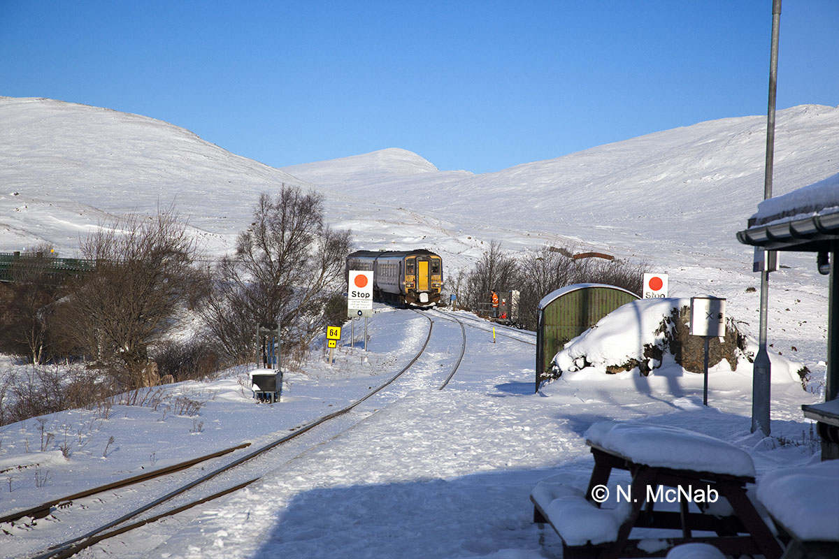 8C On A January Morning And Two Coach 156DMU Enters Rannoch Station The Engineer Beside Train Has Just Released Frozen Points
